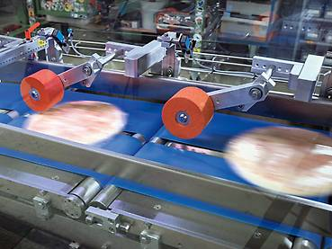 Shock-frozen and shrink-wrapped pizzas on the depositor conveyor