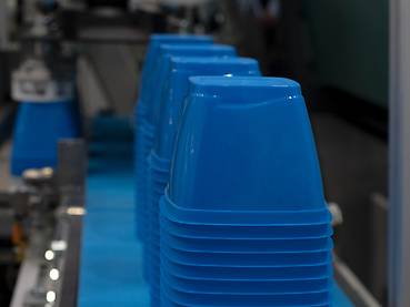 Conveyor belt with blue stacked plastic cups