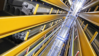 A view of the yellow-painted aisles of a high-bay warehouse where long goods (tubes, etc.) are stored