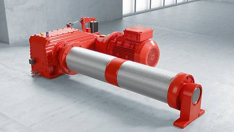 Red industrial gear unit on a rope drum against a concrete background