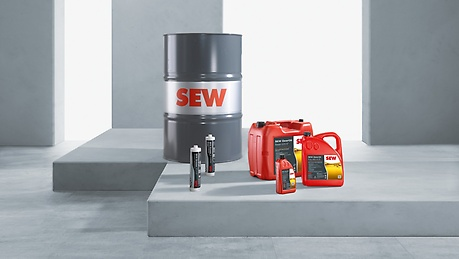 gray oil barrel, two red oil canisters, two grease cartridges in front of gray concrete background